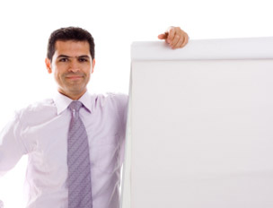 Spanish man standing next to a flip chart.